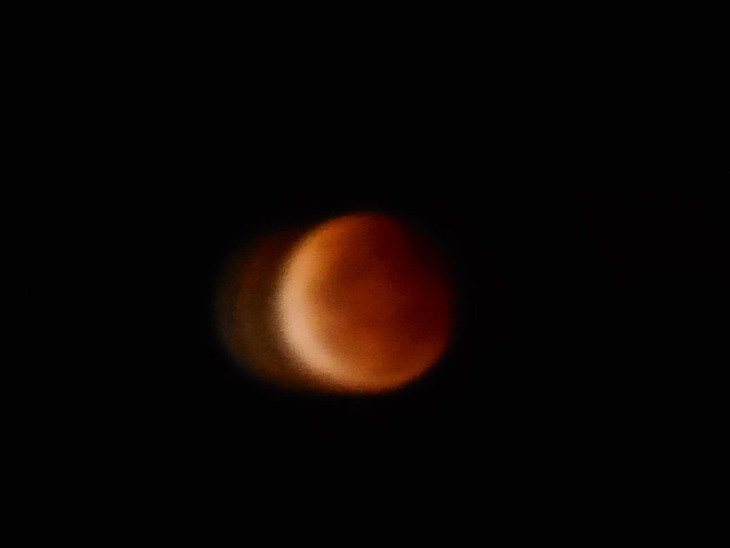 On the upper right hand side of the photo you can just make out a darker red shadow starting to move across the face of the moon. 8.53pm EDST, 8 October 2014