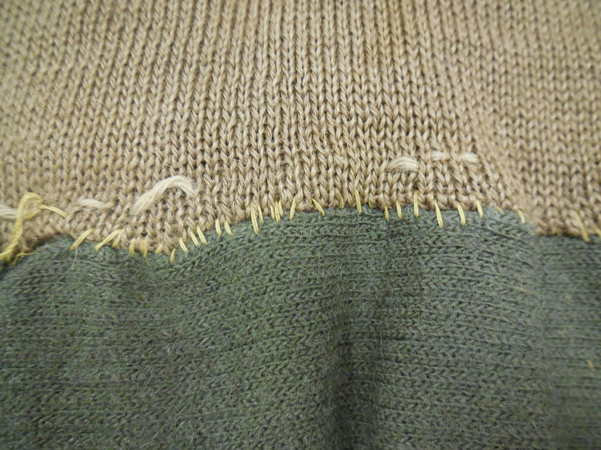 Where the puttees (green) join the central section (fawn) of the Burnett garment.
